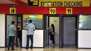 Ihmisiä lentokentän passintarkastuspisteillä. Yllä suuri espanjan- ja englanninkielinen opaste.