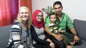 Linda Helisto istuu sohvalla yhdessä Al Radin perheen kanssa