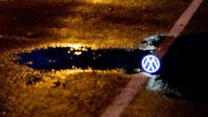 Volkswagenin mainoskyltti heijastuu vesilätäköstä Saksan Wolfsburgissa.