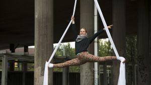 Ilona Huuhtanen esittelee taitojaan Hämeentien sillan kaiteesta roikkuvassa kankaassa.
