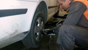 Mies vaihtaa auton takarengasta.