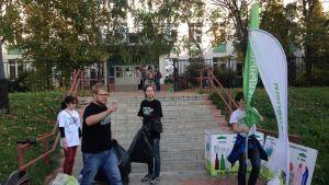 Ympäristöliike Razdelnyi sbor kerää viikonloppuisin lajiteltuja jätteitä Moskovan asuinalueilla. Neljä nuorta ihmistä mustissa ja valkoisissa paidoissaan rakennukseen johtavien portaiden edessä. Kuvan vasemmalla laidalla yksi nuorista laittaa ympäristöjärjestön vihreää lippua maassa olevaan telineeseen, jossa on jo valkoinen samankaltainen lippu.