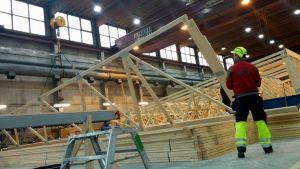 Työmies nostaa nosturilla kattotuolia