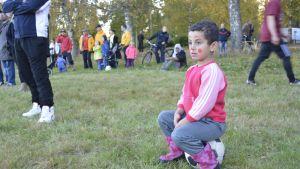 Turvapaikanhakijalapsi istuu jalkapallon päällä.