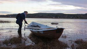 Ronja Kiira veneen kanssa joen rannalla.