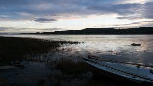 Vene joenrannassa aamuhämärässä.
