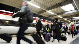 Matkustajia Eustonin asemalla, Lontoossa.