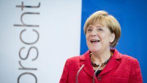 Hymyilevä, punapukuinen Merkel.