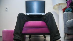 Mies istuu kannettava tietokone sylissään.