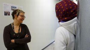 Virpi Pakisjärvi puhuu turvapaikanhakija kanssa