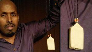 Wali Hashi roikuttaa valkoista suurta amulettia kädessään.