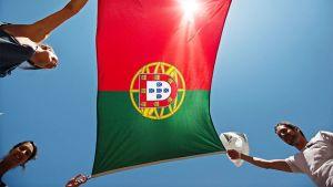 Kolme henkilöä pitää Portugalin lippua.