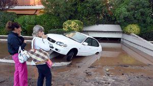 kaksi naista katsoo autoa, jonka perä on uponnut veteen