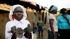 Nainen myy hiiliä tienatakseen elantoa 11-henkiselle perheelleen Manyattan slummialueella Kisumussa, Keniassa. Kuva on otettu toukokuussa 2014.