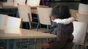 Pieni turvapaikanhakijatyttö vastaanottokeskuksessa tyhjän pöydän ääressä.