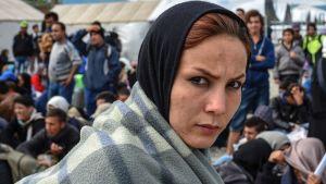 Kaunis huivipäinen nainen huopaan kietoutuneena katsoo tiukasti kameraan. Taustalla seisoo ja istuskelee muita turvapaikanhakijanaisia ja -miehiä.