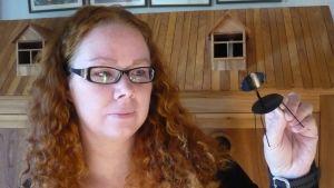 Nukkekotitaituri Maria Malmström näyttää Onnelin ja Annelin talveen kokeeksi tehtyä Tapiovaaran Lukki-tuolia 1:10.