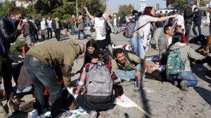 Ihmiset auttoivat loukkaantuneita räjähdyspaikalla päärautatieaseman läheisyydessä Ankarassa.