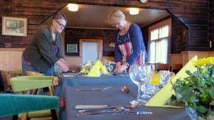Kaksi naista asettelevat ruokailuvälineitä pöydälle hirsisessä tuvassa