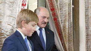Aljaksandr Lukašenka äänestyspaikalla nuorimman poikansa Nikolain kanssa Minskissä sunnuntaina.