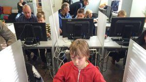 Koululaiset istuvat tietokoneella ja harjoittelevat koodaamista. Osa on yksin, osa vanhempiensa kanssa.