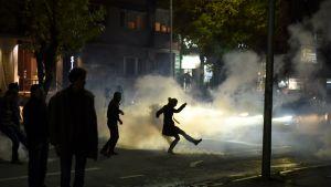 Opposition kannattaja potkaisi poliisin heittämämää kyynelkaasupulloa Pristinassa 12. lokakuuta.
