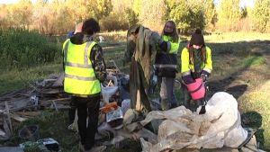 Joukko työntekijöitä raivaa pois palstaviljelmille jätettyjä tavaroita.