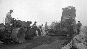 miehet levittävät asfalttia ja perässä tulee tiejyrä