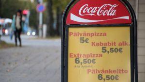 Pizzojen hintoja joensuulaisen pizzerian katumainostelineessä.