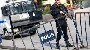 Aseistettu poliisi pommi-iskujen tapahtumapaikalla Ankarassa.