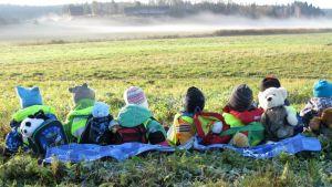 Lapsia pellon laidalla katsomassa usvaa.