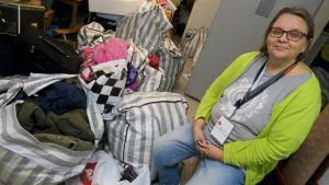 Nainen istuu varastossa