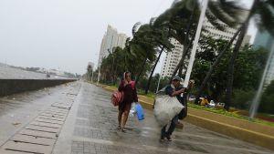 Filippiiniläisiä kantamassa omaisuuttaan taifuuni Koppun raivotessa Manilassa, Filippiineillä 18 lokakuuta.