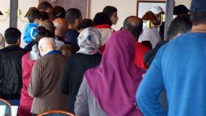 Ryhmä turvapaikanhakijoita ruokajonossa Forssan hätämajoitusyksikössä