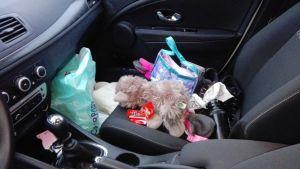 Auton pelkääjänpaikalle on kertynyt leluja, juomapullo, vaatteita ja karkkipapereita