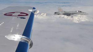 Sveitsiläinen F-18-hävittäjä harjoittelemassa tarkastuslentoa, toisen lentokoneen siipi näkyy kuvassa.