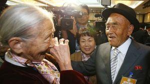 Kameramies kuvaa vanhaa hattupäistä miestä ja huivikaulaista naista. Molemmat hymyilevät leveästi.