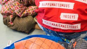 Vapaaehtoinen ja lapsi Suonenjoen hätämajoituskeskuksessa.