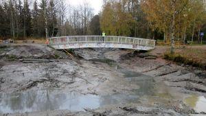 Nainen seisoo kaukana valkoisella sillalla ja ihmettelee tyhjää lammenpohjaa