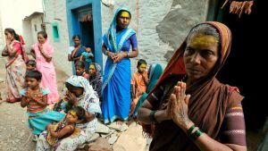 Intilaisia naisia ja lapsia kädet yhteen liitettyinä. Heidän otsansa on maalattu keltaisiksi.