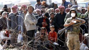Syyrialaiset turvapaikanhakijat odottavat pääsyä pakolaisleiriin Turkissa.