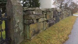 Massiivinen kiviaita kirkon ja hautausmaan ympärillä.