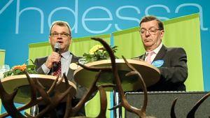 Juha Sipilä ja Paavo Väyrynen esiintymislavalla pöytien ääressä. Juha Sipilä valittiin keskustan puheenjohtajaksi vuonna 2012. Puolueen kunniapuheenjohtaja Paavo Väyrynen ei päässyt vaalien toiselle kierrokselle.