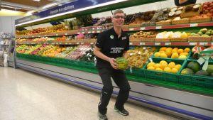 Liikuntaneuvoja tekee kykky-liikettä meloni sylissään ruokakaupassa