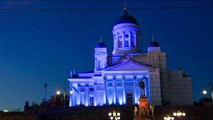 Siniseksi valaistu rakennus.