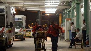 Ensihoitajat työntävät paareja. Taustalla ambulansseja.