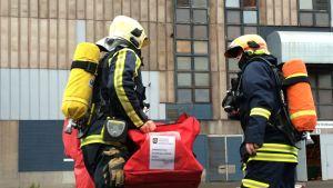 Palomiehet kantavat varustelaukkua tehtaan pihalla.