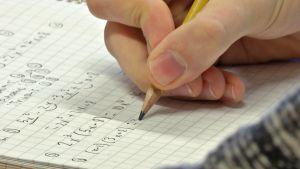 Oppilas kirjoittaa matematiikan tehtävää vihkoon