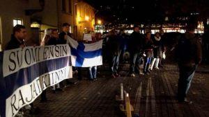 Mielenosoittajat kaupungintalon ulkopuolella. Bannerissa lukee Suomi ensin - rajat kiinni.