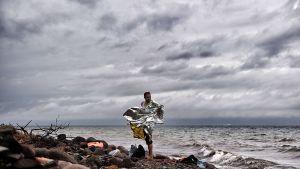 Mies seisoo lähellä rantaviivaa hopeafolioitu viitta yllään.